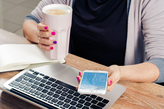 User Experience: image depicts person's arms, one (with pink and purple nail polish) holding a beverage, and the other holding a phone with an app open